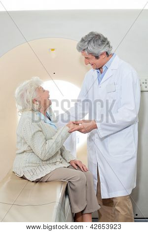 Senior female patient looking at mature male doctor while sitting on CT scan machine