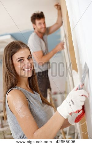 Beautiful young woman DIY at home, looking at camera, smiling.