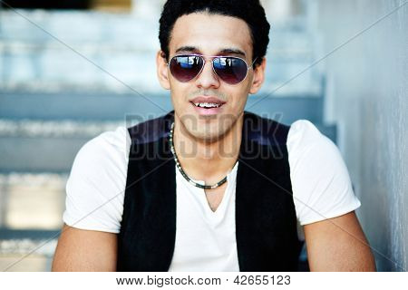 Portrait of handsome guy in sunglasses looking at camera