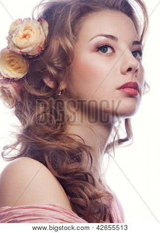 Portrait of beautiful girl with roses in the hair