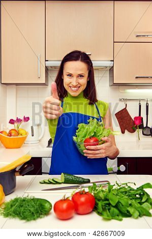 smiley woman holding fresh salad and showing thumbs up