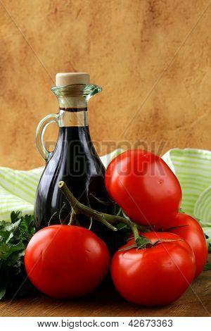 botella de vinagre balsámico y tomates frescos