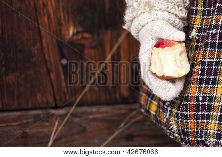 Bitten red apple in hand on the wooden background