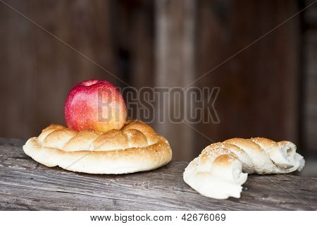 Red apple and pretzel on wooden rustic background