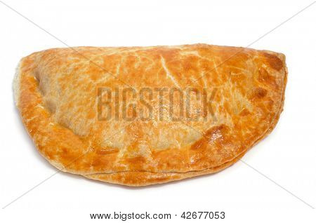 closeup of an empanada, a cake stuffed with vegetables and meat