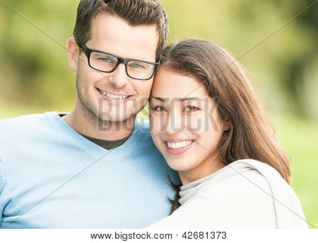 Portrait of happy young man and woman in park.