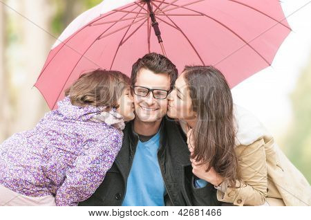 Portrait of happy family of three outdoor.