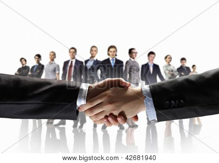 business handshake against white background and standing businesspeople
