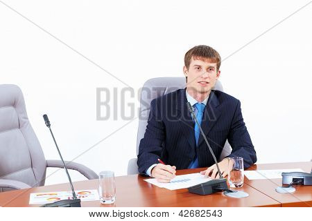 Image of young businessman sitting at table at business meeting
