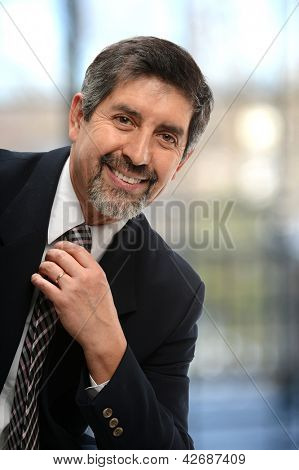 Mature Hispanic businessman smiling isolated on a white background