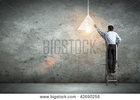 Image of businessman drawing lamp on wall