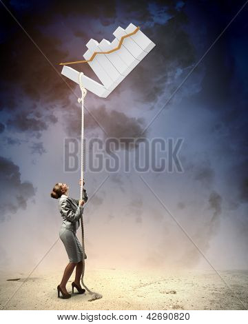 Image of businesswoman climbing the rope attached to diagram aloft