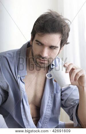 Interior portrait of a hot looking relaxed sexy male model with a cup of morning coffee