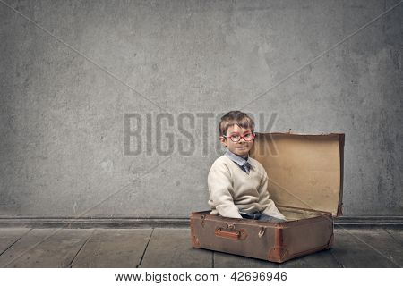 little child sitting in a vintage suitcase