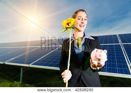 Photovoltaic system with solar panels for the production of renewable energy through solar energy, the investor is in front with a piggybank and a sunflower