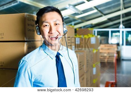 Young man in a suit with a headset in a warehouse, he is from the Customer Service