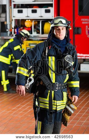 young fireman in uniform standing in front of firetruck, he is ready for deployment