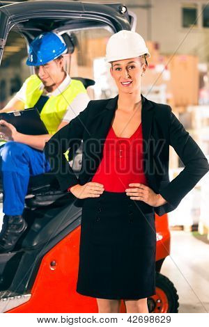 Forklift driver with clipboard at warehouse of freight forwarding company, female super visor or dispatcher looking at the viewer