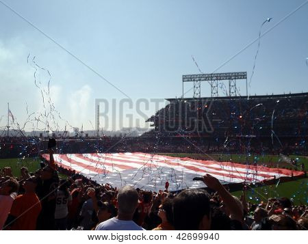 Streamers Fly In The Air As People Cheer With Large Usa Flag Held Across The Outfield By A Line Of P