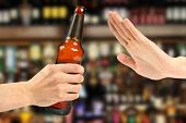 stock photo of rejection  - hand reject a bottle of beer in the bar - JPG