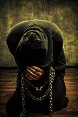 stock photo of warlock  - Miserable monk praying on his knees in dark room - JPG