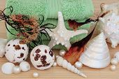 Seaweed spa accessories with bath bombs, towels, sea shells and pearls over bamboo background.