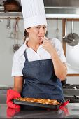 foto of finger-licking  - Portrait of happy female chef licking finger while holding bread tray in kitchen - JPG