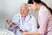 foto of radiogram  - Senior male doctor and female patient looking at ultrasound print - JPG
