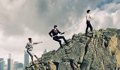 stock photo of pulling  - Image of three businesspeople pulling rope atop of mountain - JPG