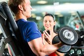 stock photo of dumbbells  - Man or Bodybuilder with his personal fitness trainer in the gym exercising sport with dumbbells - JPG