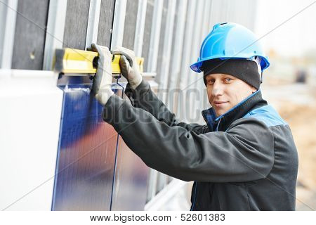 Plasterer builder worker with level examining metal profile facade plate installation