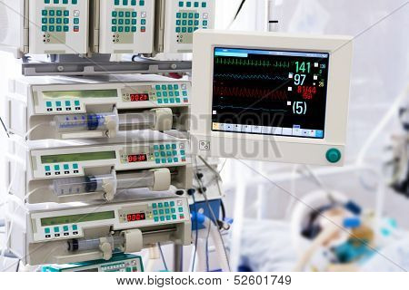 Patient with monitor and infusion pumps in an intensive care unit