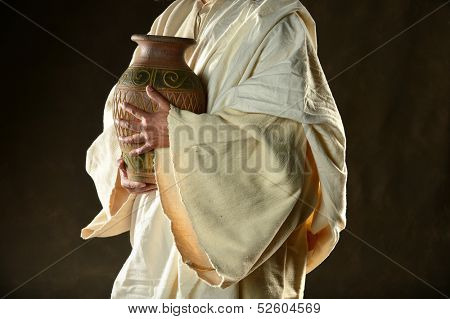 Jesus hands holding jar over dark background