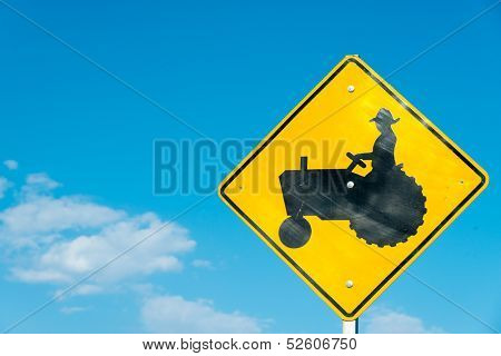 A yellow tractor crossing sign with a sky blue background