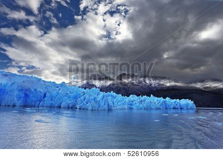 The clouds covered the sun cold. Grey glacier moves down the water of the lake. Chilean Patagonia. National Park Torres del Paine. Lake and Glacier Grey