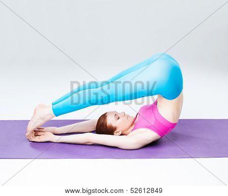 young beautiful yoga posing  on a studio background