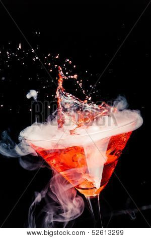 red cocktail with splash and ice vapor
