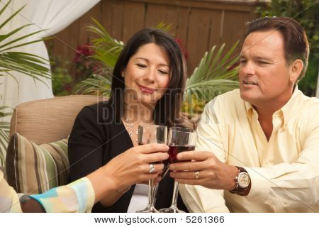 Three Friends Enjoying Wine On The Patio