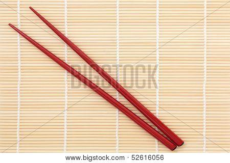 Red chopsticks over bamboo mat background.