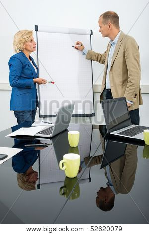 Side view of two managers discussing a diagram on a flipchart in conference room