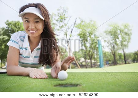 Smiling young woman lying down in a golf course and flicking ball into hole