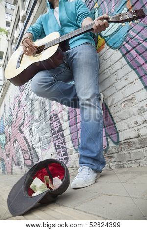 Young street musician playing guitar and busking for money