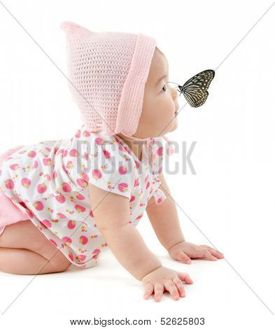 Butterfly flying to Asian baby girl nose, isolated on white background
