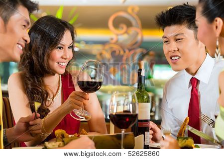 Two Asian Chinese Couples or friends or business people toasting during dinner or lunch in a elegant restaurant with red wine glasses