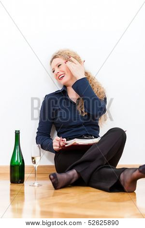 Young business woman is sitting at home on the floor and takes a break at after hour