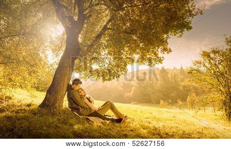 Loving couple under a big tree in the park in autumn