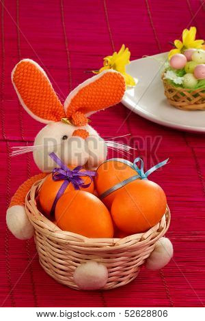 Cute orange bunny - basket with easter eggs on red mat