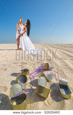 Groom and bride on the beach with cans attached
