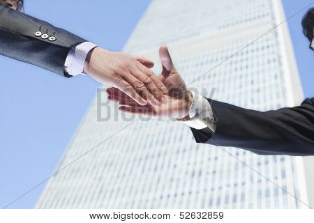 Close-up of two business people shaking hands by the World Trade Center in Beijing