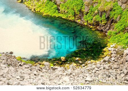 Clear and clean spring water from the mountains is being mixed with dirty water from wild glacial river Jokulsa a Fjollum in Iceland
